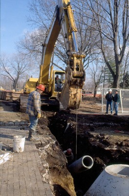 Workers install pipes for new library construction.