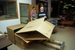 Student workers and staff prepare boxes for moving library materials.