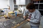 <em>A Touch of Glass</em> restoration artist removes damaged pieces from one of the Pembroke Windows.