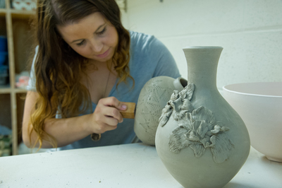 Art Major  Annastasia Calvert, '14 working on pottery in the art building lab.